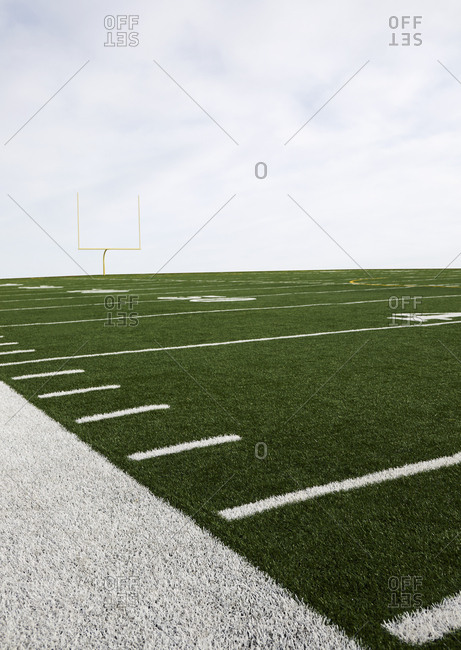 Overcast sky above American football field and goal post