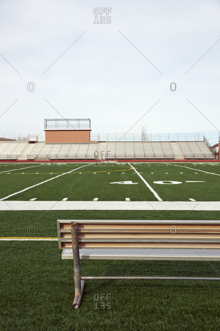 American football field with bench in foreground and empty bleachers in background