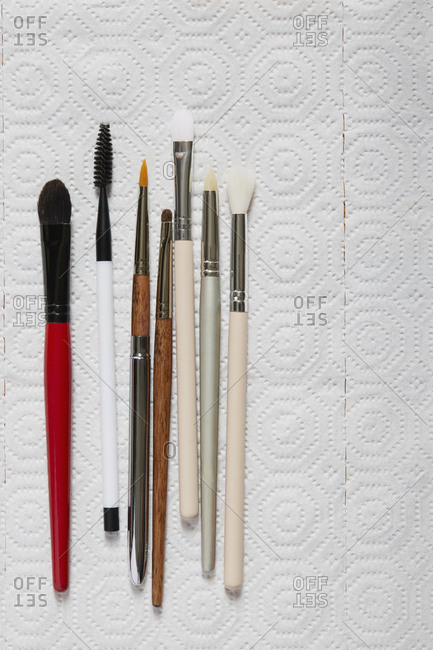 Various make up brushes lined on paper towel
