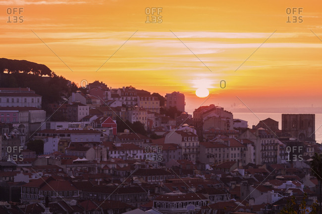 Portugal, Lisbon, Sun rising above Old Town of Lisbon