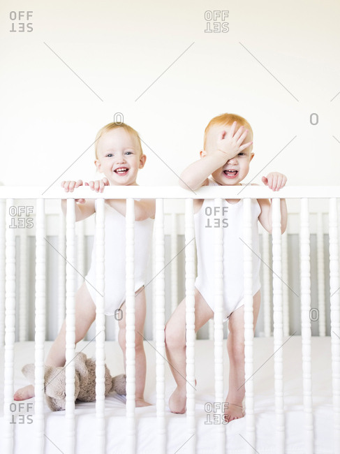 Twin brothers standing in crib