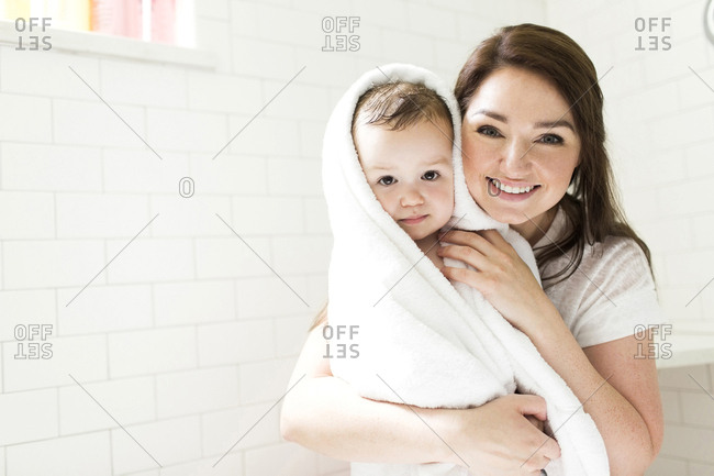 Mother wrapping son in towel in bathroom