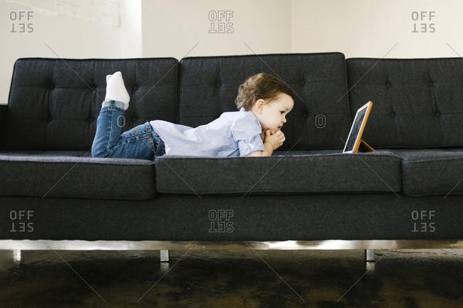 Young boy lying on sofa
