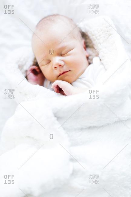 Baby boy sleeping in white blanket