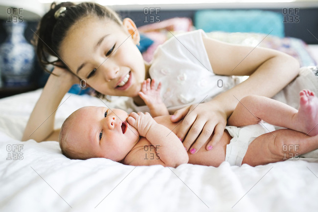 Girl lying in bed beside brother