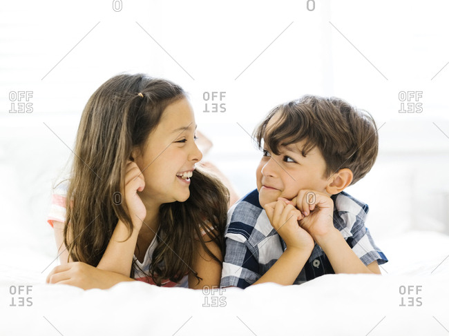 Siblings lying in bed side by side