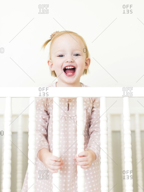 Content small girl with mouth open standing in crib