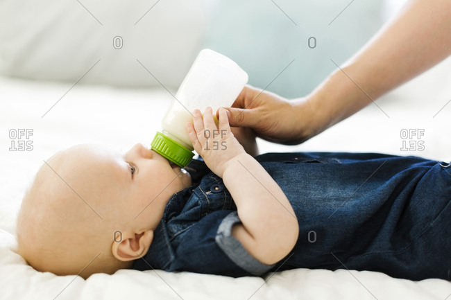 Side view of baby boy being fed by woman with bottle of milk
