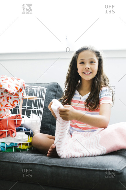 Girl with laundry sitting on sofa