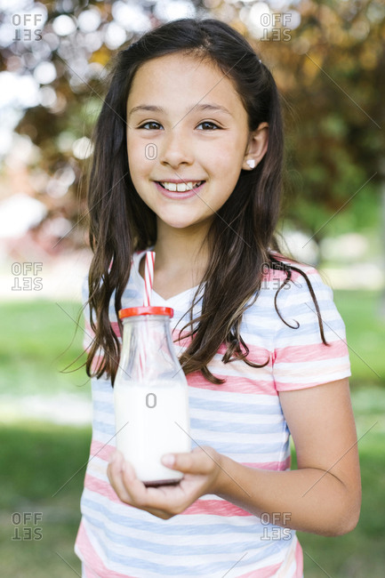 Girl in park holding glass of milk with straw
