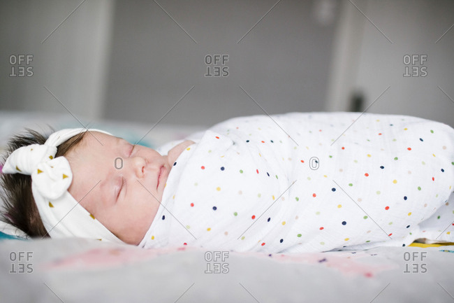 Baby girl months wrapped in blanket sleeping on bed
