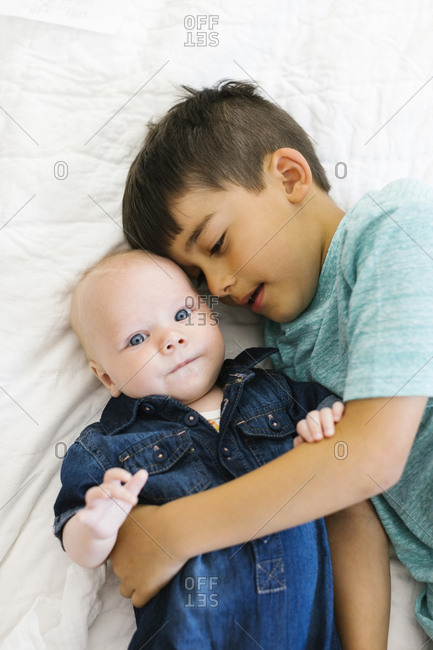Two brothers months lying on bed and hugging