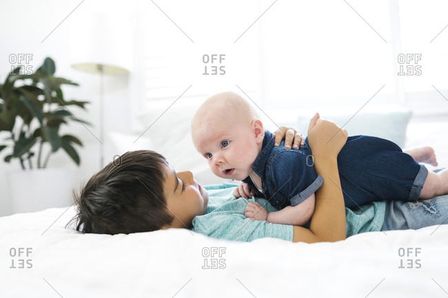 Boy lying on bed and embracing brother