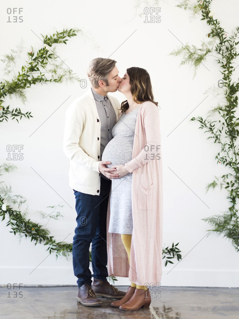 Portrait of men and pregnant woman kissing