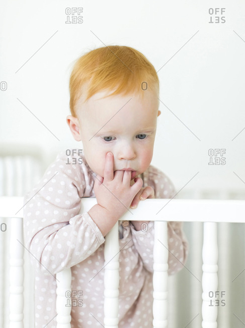 Portrait of girl holding fingers in mouth