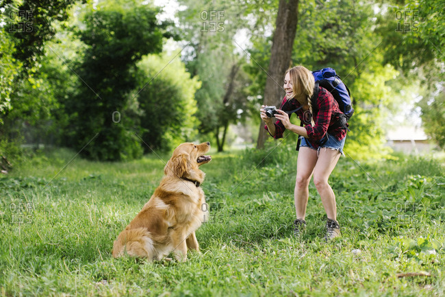 Woman photographing dog on hiking trip