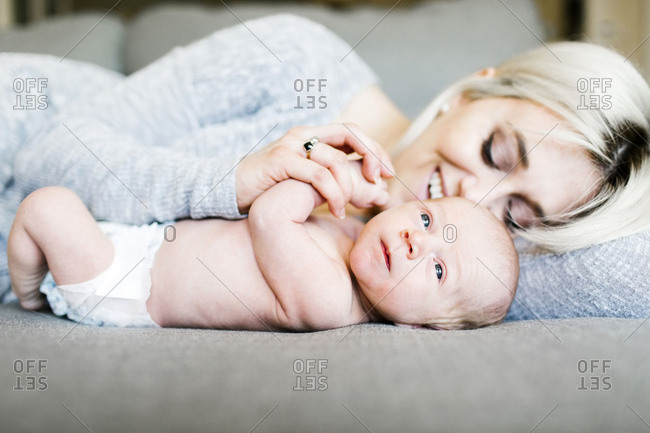 Mother with newborn months lying on sofa