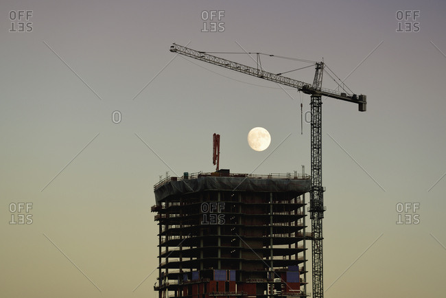 USA, Colorado, Denver, Full moon in background of skyscraper construction site at dusk