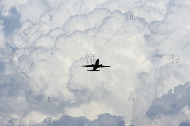 Airplane in sky with clouds in background