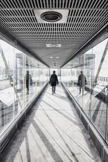 USA, Massachusetts, Boston, Woman walking down glass and metallic walkway at train station