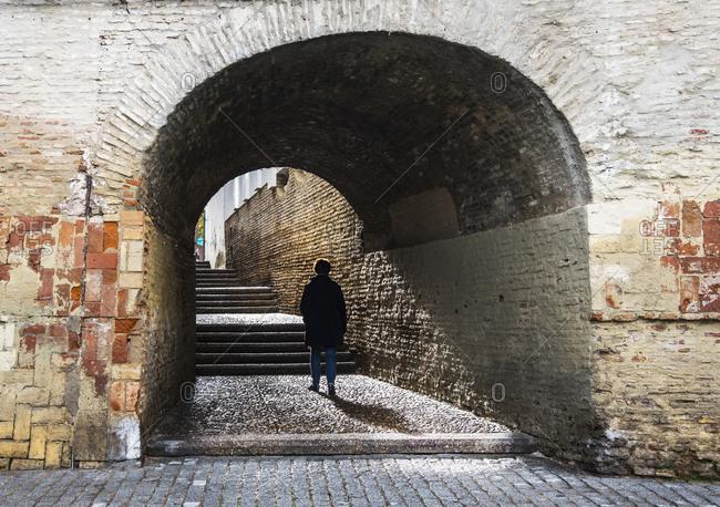 Spain, Seville, Triana, Woman walking through Cajellon De La Inquisicion