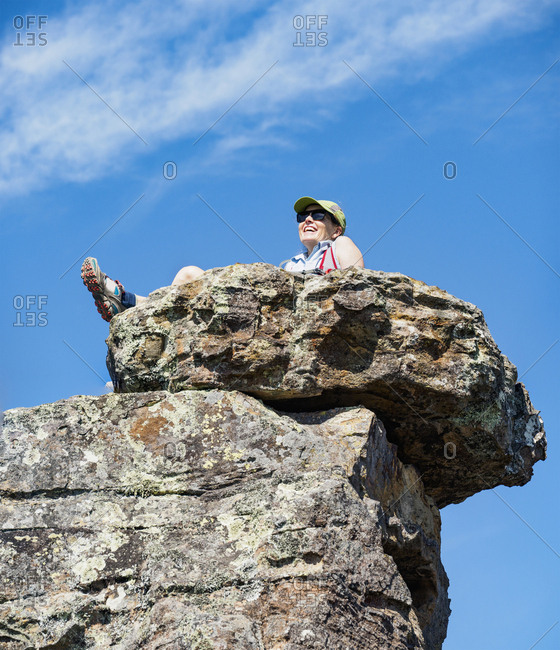 Low angle view of woman sitting on rock