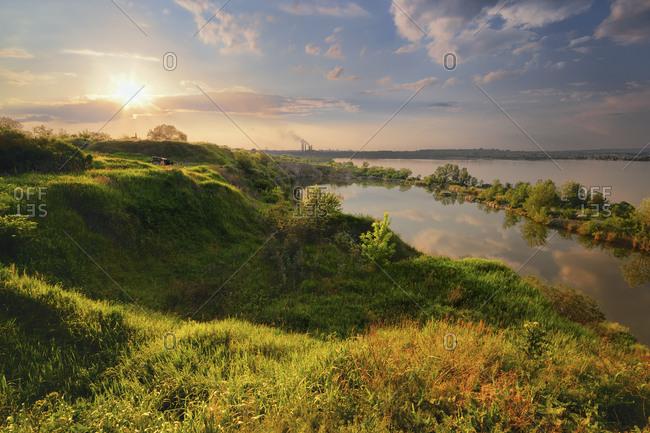 Ukraine, Dnepropetrovsk, Landscape with pond and hills at sunset