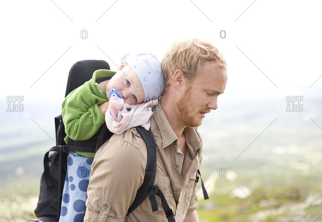 Father hiking with daughter in baby carrier