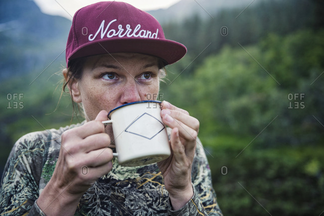 Woman drinking from metal cup