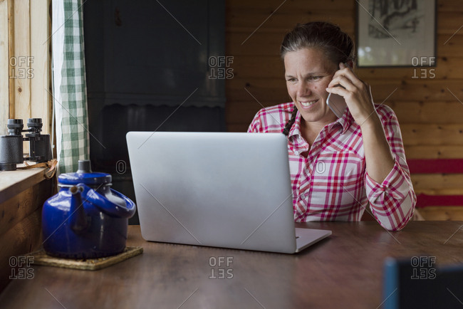 Woman at home on the phone using laptop