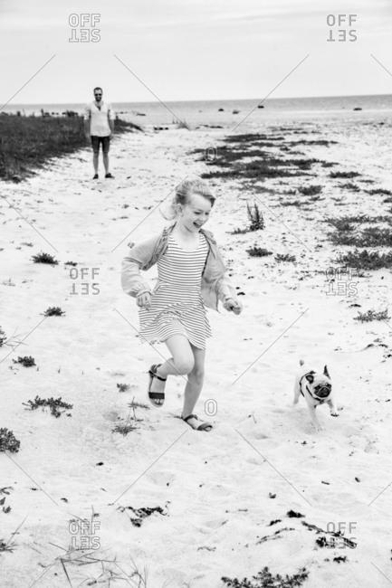 Girl running with dog at sea