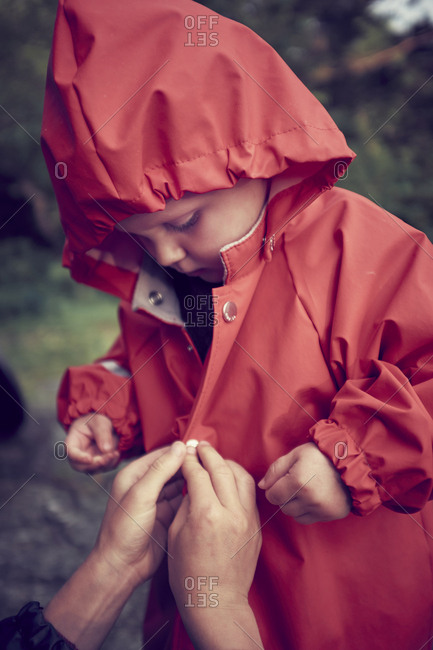 Helping boy with raincoat
