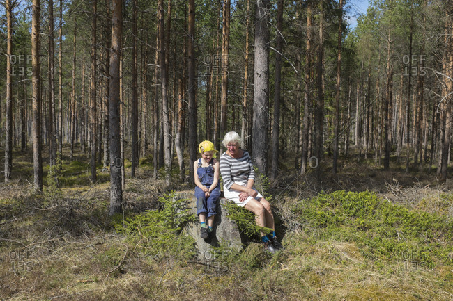 Grandmother with granddaughter sitting in forest