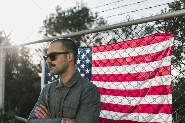 A person with the arms crossed standing at the chain wire with the US flag,