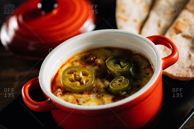 A red pot filled with molten cheese and spicy sausage, Mexican cuisine,