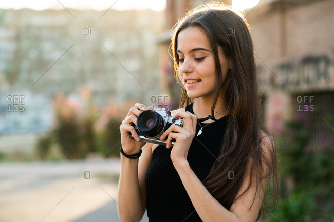 Attractive young girl setting a camera in the street, Horizontal outdoors shot,