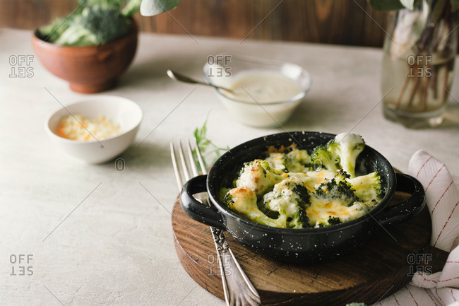 Broccoli with bechamel sauce and gratin cheese, on wooden board