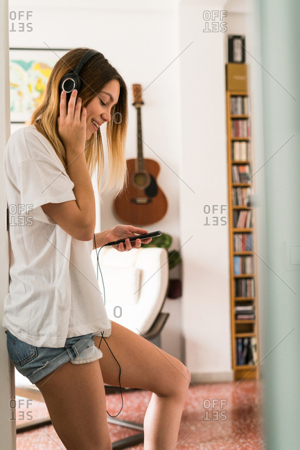 Cheerful woman in doorway listening to music with the smartphone,