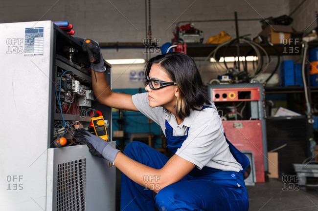close-up of a female mechanic using a multimeter to test an electric motor coil from a compressor engine