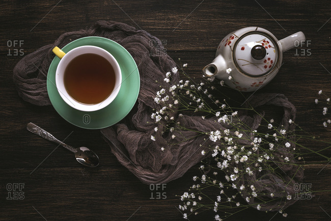 Cup of tea with Floral background with red and white tulips and daisies, and green leaves on brown background, Flat lay, top view