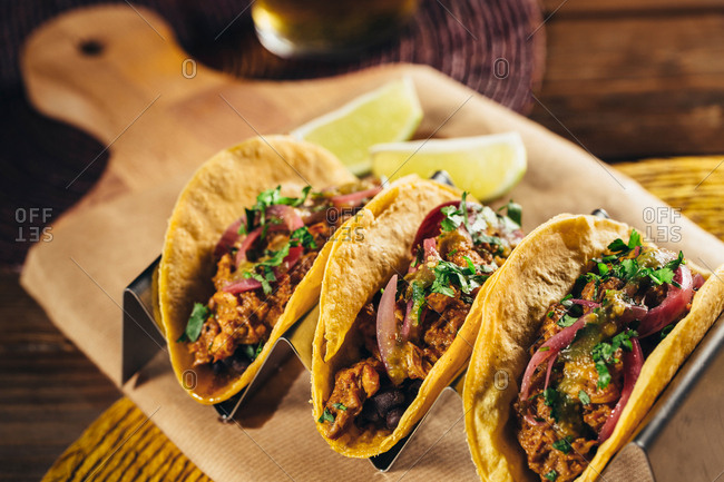 Delicious mexican cochinita pibil tacos on a wooden board with beer glass,