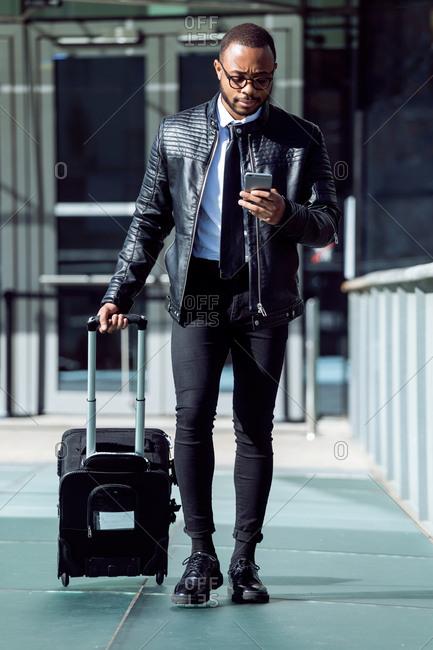 Elegant stylish male using phone while walking with black suitcase on urban background,