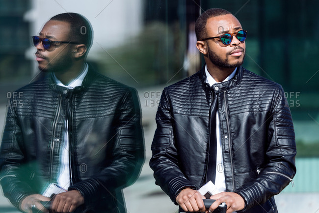 Elegant stylish man in black leather coat and sunglasses reflected in the building,