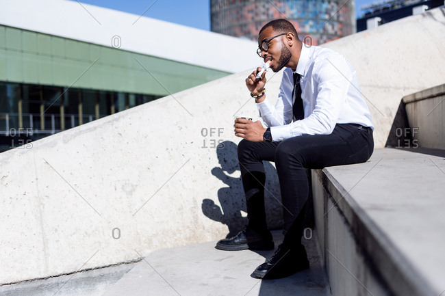 Elegant young man sitting on stairs drinking coffee and eating snack,