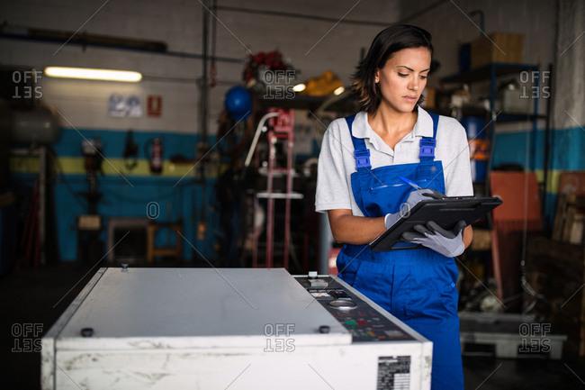 female mechanic checking machine status