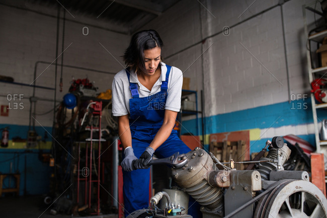 female mechanic fixing a compressor engine using a wrench