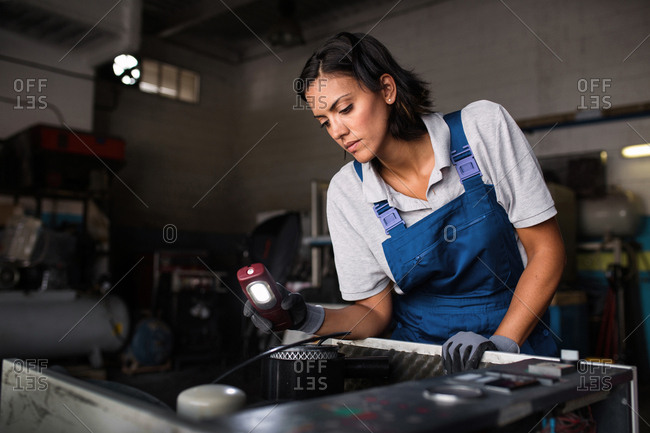 female mechanic looking for a fault on a compressor engine using a flashlight
