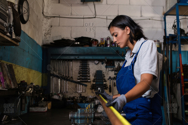 female mechanic measuring a tube in a garage