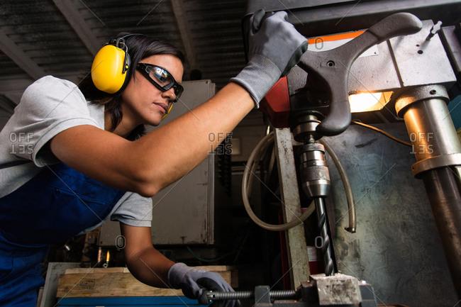 female mechanic operating a column type drill
