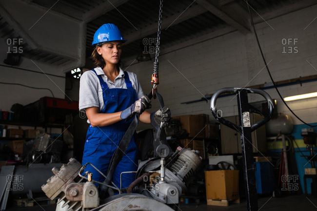 Female mechanic operating a hoist to lift a compressor engine